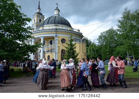 St. Petersburg Russia - May 22 2016: People in national Russian suits are dancing at the at the festival of folk culture. Nicholas churchyard church of the prophet Eli in St. Petersburg 18th century.