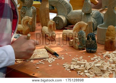 St. Petersburg Russia - May 22 2016: Master class of woodcarving on a counter with self-made wooden toys in national style at a fair