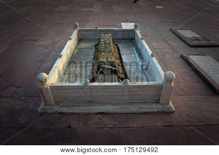Muslim stone grave covered with a handkerchief in the Holy city of Fatehpur Sikri. India.