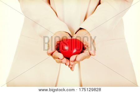 Elderly woman holding heart model on open palms