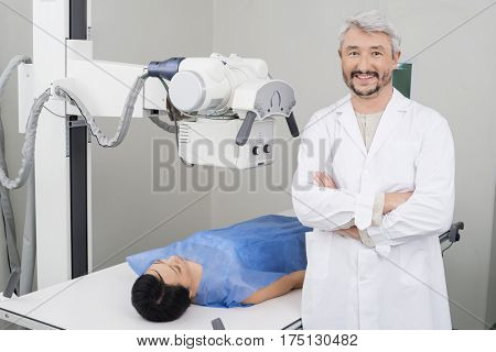 Confident Radiologist Standing By Female Patient Undergoing X-ra