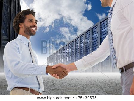 Digital composition of two businessman shaking hands with each other and servers against sky in background