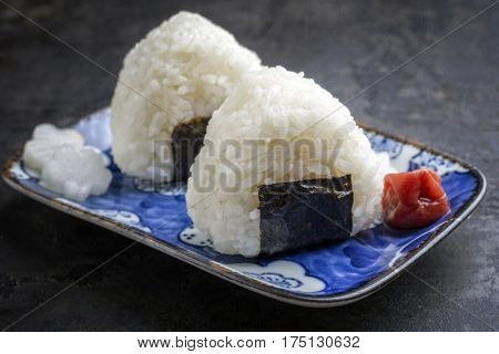 Traditional Japanese Onigiri with Umeboshi as close-up on a bowl