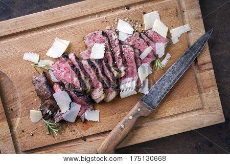 Traditional Italian Tagliata Steak with Parmesan as close-up on cutting board