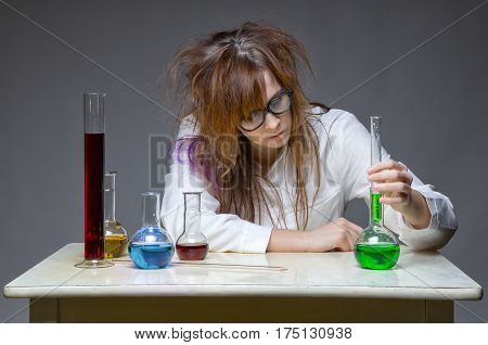 Working scientist with glass flask on gray background