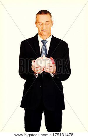 Confused businessman holding piggybank