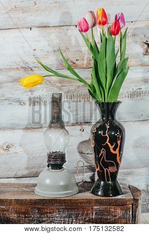 Old wooden background with tulips in vase and kerosene lamp