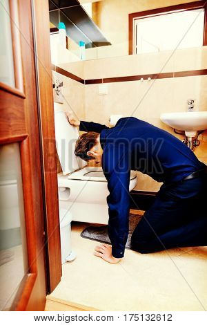 Young drunk or sick man vomiting