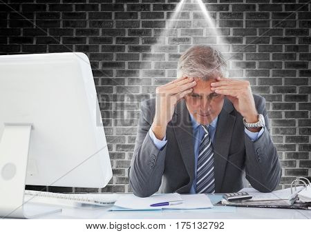 Digital composition of a stressed businessman sitting at computer desk against brick wall