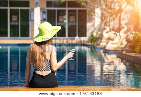 Woman in swimsuit relaxing with cocktail on chaise-longue greenery tone 2017
