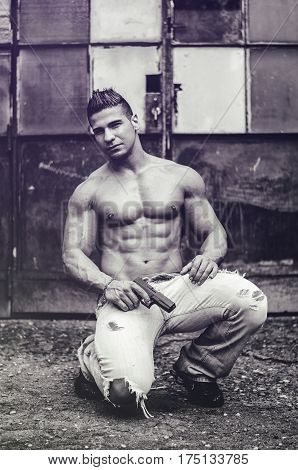 Menacing, muscular young man shirtless holding a handgun in his hand, outdoor