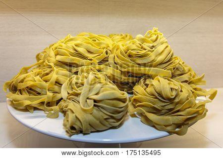 Uncooked Tagliatelle Italian Pasta Shown On White Dish
