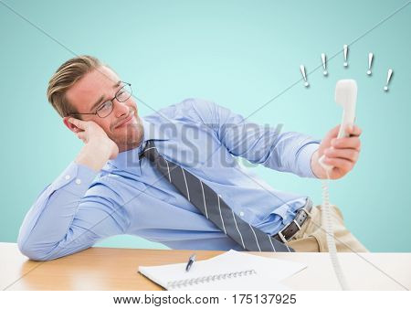 Irritated businessman holding telephone receiver at desk in office