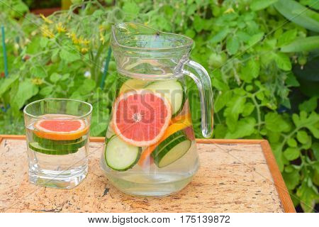 Grapefruit cucumber orange detox water in pitcher and glass