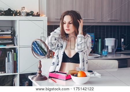 Portrait of young beautiful Caucasian white girl woman in lingerie doing her makeup in front of the mirror in morning at home candid lifestyle natural light toned with filters