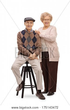 Full length portrait of an elderly man sitting on a chair with an elderly woman standing next to him isolated on white background