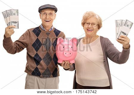 Cheerful senior couple with bundles of money and a piggybank isolated on white background