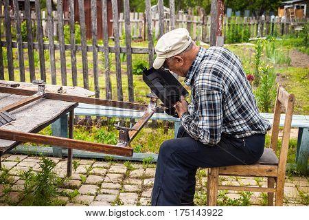 Senior man welding metal structure at his garden