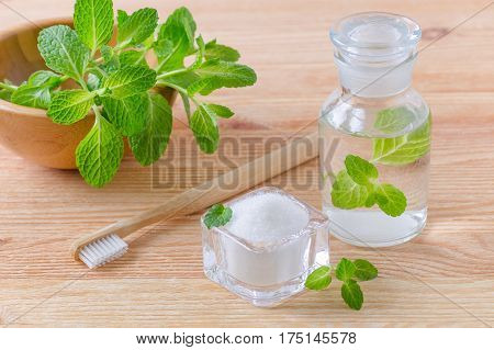 alternative natural mouthwash bottle with toothpaste xylitol soda salt and wood toothbrush closeup mint on wooden background