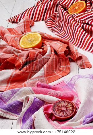 Sliced Sicilian blood red orange, grapefruit and lemon in the center colourful cloth napkin order like vertigo.White wooden table
