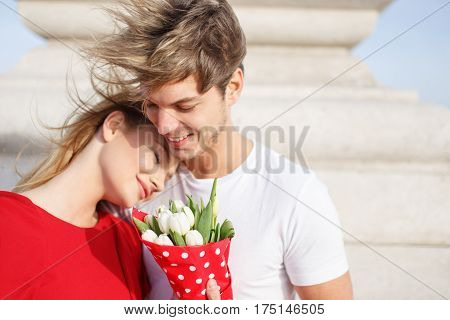 Happy young caucasian couple cuddle outdoor smiling
