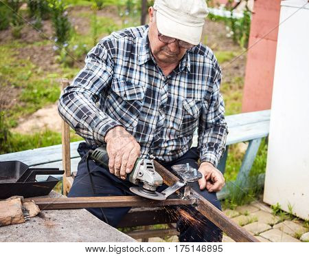 Senior man using grinder for his construction