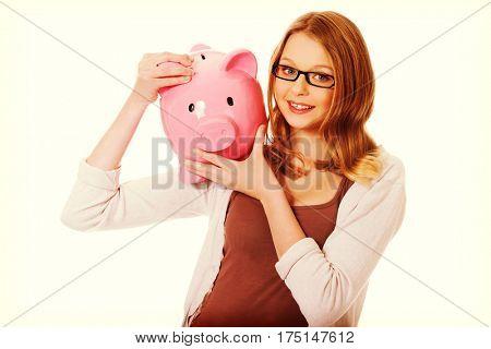Young woman holding piggybank