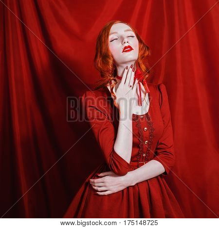 A woman posing with red curly hair in a red dress and retro makeup on a red background. Red-haired girl posing with pale skin blue eyes a bright unusual appearance red lips and red ribbon around neck. Red magic posing