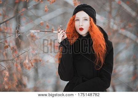 A woman with red hair in a black coat on background of a winter forest with a mouthpiece in hand. Red-haired girl with bright appearance with a turban on her head with a cigarette in mouthpiece. Smoking aesthetics with mouthpiece