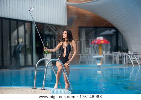 Gorgeous Smiling Woman In A Black Sexy Swim Suit Makes Selfie Photo With Selfie Stick On Luxury Reso