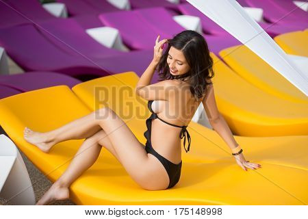 Beautiful Sensual Woman In A Black Swimsuit On A Yellow Lounger Outdoors. View From Behind, Her Face