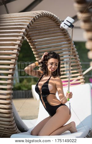 Attractive Happy Female In A Black Swimsuit Posing And Makes Selfie Photo With Selfie Stick On Origi