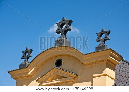 Jewish stars on the roof with cornice and sky background