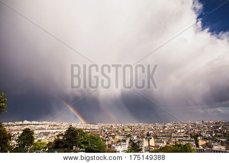 View of Paris from the hill of Montmartre. Travel through Europe. Attractions in France. Sunny european Paris. Clouds in the sky in european city. Double Rainbow. Thunder Sky. European town