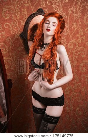 Portrait of a woman with long red curly hair in black lingerie and choker on her neck. Red-haired girl with pale skin bright unusual appearance and red lips and a thin waist on background of a mirror
