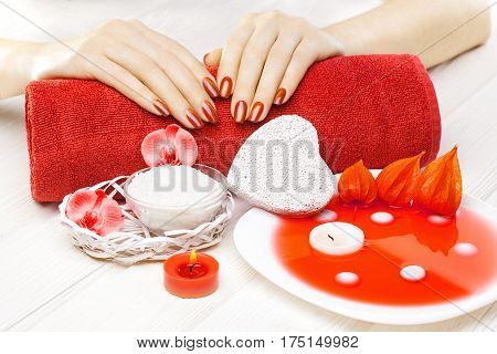 beautiful red manicure with oil and candles, red orchid flower and towel on the white wooden table.
