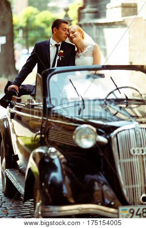 A Wedding Couple Daydreams Sitting On Black Retro Cabriolet