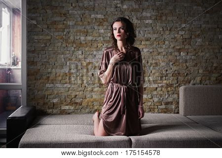 Girl PinUp with brunette hair and retro make-up with red lips in a bathrobe on a dark background. Girl sitting on the bed. Vintage image.