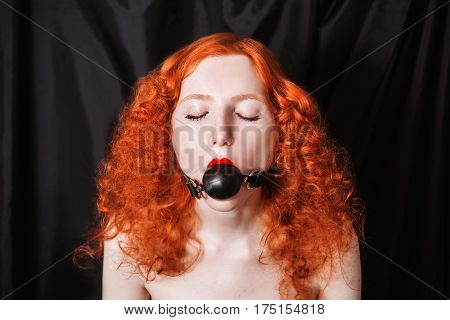 Violence woman with long red curly hair gagged. Red-haired girl with pale skin blue eyes a bright unusual appearance on a black background. The frightened look. BDSM