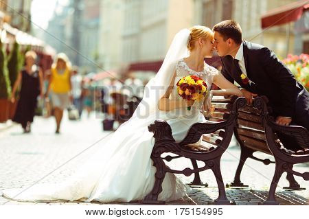 Bride And Fiance Kiss Sitting On Different Old Benches