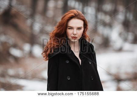 Portrait of a glamorous  sensual girl with long red hair in black clothes. A  sensual woman in a black coat posing on a background of winter autumn nature. Female street fashion style. Beautiful elegant  sensual model