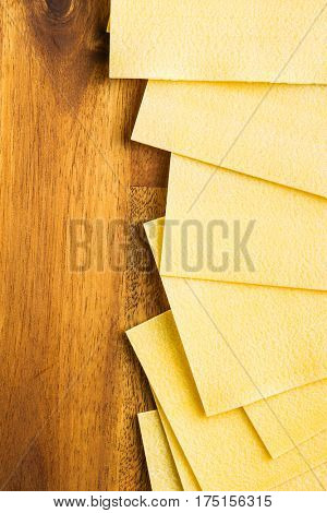 Raw lasagne sheets on wooden table. Top view.