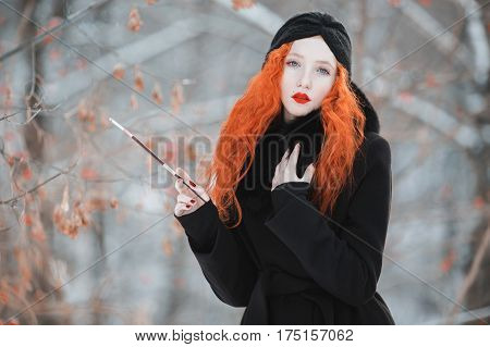 A woman smoking with red hair in a black coat on background of a winter forest with a mouthpiece in hand. Red-haired smoking girl with bright appearance with a turban on her head with a cigarette. Smoking aesthetics