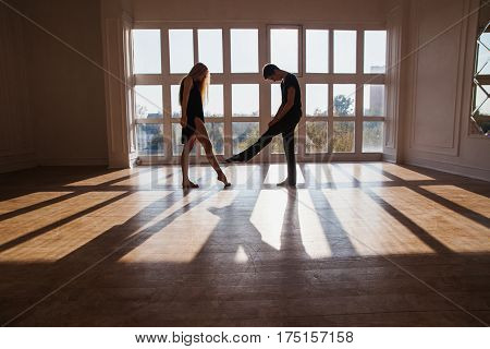 A young boy and girl with long blond hair standing in front of the window. Dancers during a workout. Problems and difficulties in relations. The difficult situation in life. Conceptual dancers photography