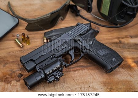 pistol with flashlight and sunglass on wood plate