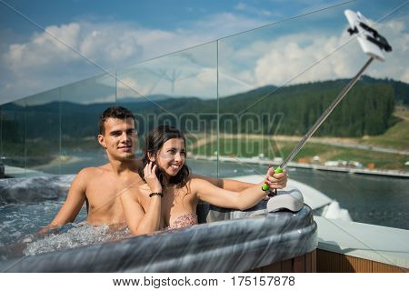 Romantic couple enjoying jacuzzi outdoors and making selfie photo on the phone with selfie stick against blurred background of nature