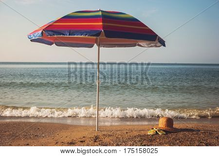 Umbrella on the beach. Seashore and sky. Away from noise and bustle. Nice place to relax.