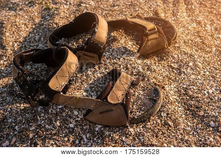 Shoes in the sand. Men's sandals of brown color. Get lost on exotic island. Escape from worries.