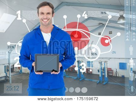 Digital composition of mechanic holding a digital tablet against digital interface in workshop