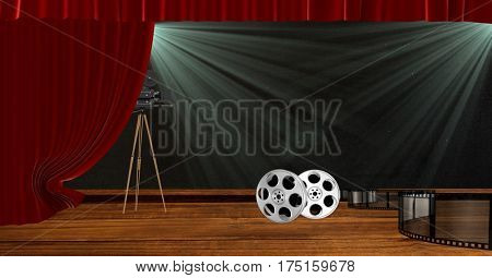 Digitally generated image of camera with film reels on stage with red drape curtains